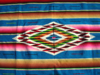 Mexican vintage textiles and Saltillo serapes, and Mexican vintage blouses and huipiles, a beautiful Saltillo serape (sarape) with a lovely turquoise background and a wonderful woolen and silk center medallion, c. 1930's. Closeup photo of the center medallion of the Saltillo serape (sarape).