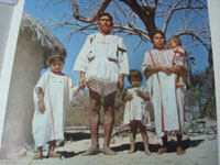Mexican vintage textiles and serapes (sarapes), and blouses and huipiles, a cotton shirt and pants set with extraordinarily fine embroidery, Santa Maria Zacatepec, Oaxaca, 1950's. Photo from a publication showing a family in the traditional clothing.