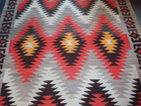 Native American Indian vintage textile, a Navajo Red-Mesa weaving, c. 1930-1940. The border shows a Tees Nos Pas influence. Very well woven with an eye-dazzler center design. A second closeup photo of the Red Mesa.