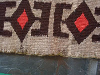 Native American Indian vintage textile, a Navajo Red-Mesa weaving, c. 1930-1940. The border shows a Tees Nos Pas influence. Very well woven with an eye-dazzler center design. A closeup photo of the edge of the weaving.