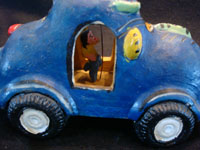 Mexican vintage pottery and ceramics, and Mexican vintage folk-art, a bright blue car or taxi, filled with happy passengers, attributed to the great folk-artist, Candelario Medrano of Jalisco, c. 1960's. A closeup photo of the side of the car.