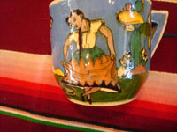 AE-1: Mexican vintage pottery and ceramics, a tea-cup and saucer with incredibly fine artwork, featuring a lovely Charra, dressed in her China Poblana costume, doing the famous dance, El Jarabe Tapatio, Tlaquepaque or Tonala, Jalisco, c. 1930. Closeup photo of the dancers on the sides of the cup.