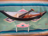 Native American Indian vintage folk art and woodcarving, a graceful and lovely model Nootka boat with oars, West Coast of Vancouver Island, British Columbia, c. 1960's. Photo from above looking down at the boat and oars.