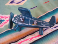 Mexican vintage folk art, and Mexican vintage woodcarvings and masks, a whimsical and lovely laquered woodcarving of an airplane with 4 happy passengers, Olinala, c. 1950's. Photo of one side of the airplane showing a passenger.