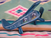 Mexican vintage folk art, and Mexican vintage woodcarvings and masks, a whimsical and lovely laquered woodcarving of an airplane with 4 happy passengers, Olinala, c. 1950's. Photo showing the second side of the airplane with passengers.