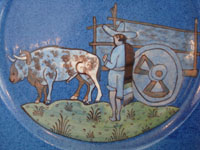 Mexican vintage pottery and ceramics, a lovely blue-glazed Tlaquepaque plate with fine artwork featuring a campesino with his faithful ox, Tonala or San Pedro Tlaquepaque, Jalisco, c. 1940's. Closeup photo of the campesino and his ox and cart.