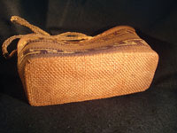 Native American Indian basket, a Northwest Coast twined purse, Tsimshian, c. 1900-10. Beautifully woven of cedar bark with geometric imbricated decoration and woven cedar bark handles. A closeup of the bottom of the basket.