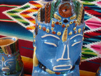 Mexican vintage pottery and ceramics, a pulque or punch set with pitcher and 5 mugs in the form of Aztec gods, c. 1940. Wonderful blue glaze with hand-painted faces and decorations on each piece. Closeup.