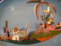 Mexican vintage pottery and ceramics, a lovely charger with a pale-blue background and excellent artwork, Tonala or Tlaquepaque, Jalisco, c. 1920-30's. The oval-shaped charger features scenes of Mexican rural life, set amidst lovely plants and foliage.  Closeup photo of the scene on the charger.