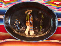 Mexican vintage pottery and ceramics, a wonderful black-ware oval charger with exquisite artwork featuring a dashing Mexican charro with his sarape and water jar, Tonala or Tlaquepaque, Jalisco, c. 1920-30's. Main photo of the front of the Tonala charger.