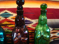 Mexican vintage devotional art, and Mexican vintage pottery and ceramics, hand-blown glass holy-water bottles in the shape of Our Lady of Guadalupe, c. 1940's. Three of the bottles have a rare metallic hue, and the fourth is a beautiful cobalt blue. Closeup photo of two of the bottles.