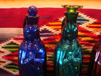 Mexican vintage devotional art, and Mexican vintage pottery and ceramics, hand-blown glass holy-water bottles in the shape of Our Lady of Guadalupe, c. 1940's. Three of the bottles have a rare metallic hue, and the fourth is a beautiful cobalt blue. Closeup photo of the other two bottles.