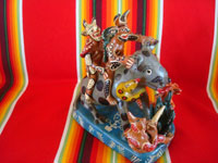 Mexican vintage folk art, and Mexican vintage pottery and ceramics, a fantastic pottery sculpture depicting a whimsical doggie being ridden by jolly devils and snakes, Ocumicho, Michoacan, c. 1960's. Main photo of the sculpture.