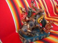 Mexican vintage folk art, and Mexican vintage pottery and ceramics, a fantastic pottery sculpture depicting a whimsical doggie being ridden by jolly devils and snakes, Ocumicho, Michoacan, c. 1960's. Another side view of the sculpture.