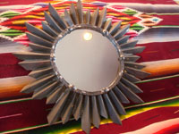 Mexican tinwork art, a wonderful tinwork-art mirror with the shape of a lovely sunburst, Mexico, c. 1950's. A side angle photo showing the mirror.