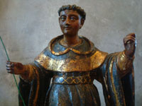 Mexican colonial devotional art, and Mexican colonial woodcarvings, a wooden statue of a saint, most likely St. Dominic, Mexico, c. 17th century. Closeup photo of the saint's face.