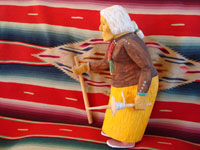 Photo, side view of Navajo wood carving by Johnson Antonio of elderly woman with cane.