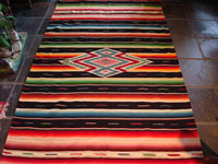 Mexican vintage textile, Saltillo sarape with black background and colorful silk center diamond, c. 1940.