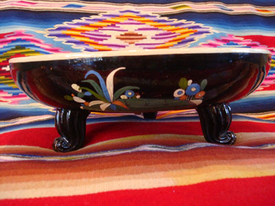 Mexican vintage pottery and ceramics, a black-ware bowl with a tri-pod base, Tlaquepaque, Jalisco, c. 1930's. The bowl has a very graceful and beautiful form, and the artwork on the bowl is very sharp and intricate. The central design is a wonderful celebration of Mexican rural life.
