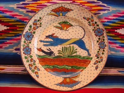 Mexican vintage pottery and ceramics, a very fine pottery plate featuring a leaping wolf, a blue bunny, butterflies and lovely foliage, with a starry-night background, from Tlaquepaque, Jalisco, c. 1920's. This is a fabulous plate and a collector's dream.