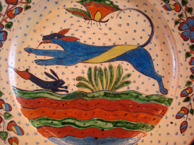 Mexican vintage pottery and ceramics, a very fine pottery plate featuring a leaping wolf, a blue bunny, butterflies and lovely foliage, with a starry-night background, from Tlaquepaque, Jalisco, c. 1920's. This is a fabulous plate and a collector's dream. The artwork is spectacular.