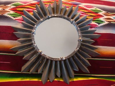 Mexican tinwork art, a wonderful tinwork-art mirror with the shape of a lovely sunburst, Mexico, c. 1950's. The mirror is lovely and will look incredibly great hanging on any wall!